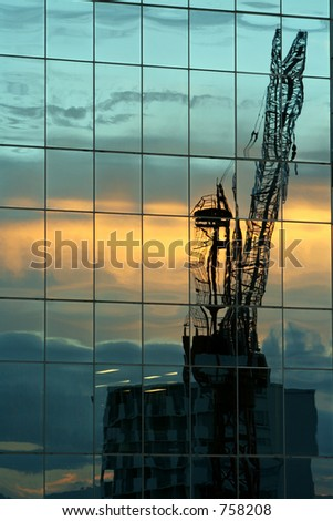 Building crane at sunset reflected in tower windows.