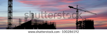 Building crane at the background of building under construction - stock photo