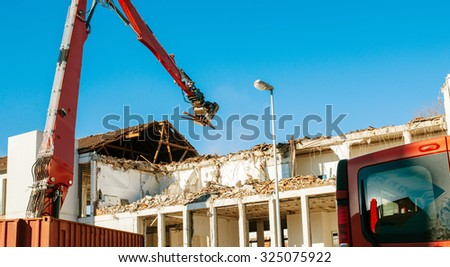 Building demolition by a heavy twisted rebars industrial machine on a red truck  - stock photo