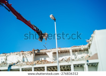 Building demolition destruction by the articulating mechanical jaws attached to an excavators arm, tearing down an old reinforced concrete building  - stock photo