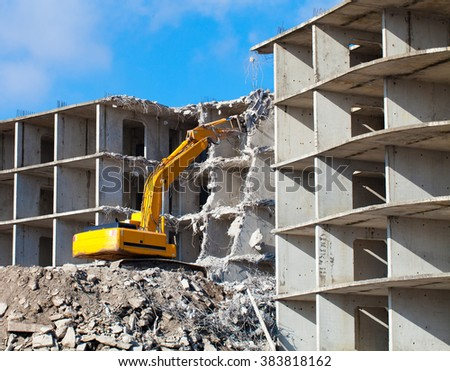 Building demolition with hydraulic excavator - stock photo