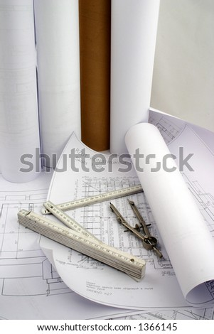Building designs, some in a rolls of paper put together with construction measure and compasses - stock photo