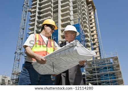Building developer and contractor discuss progress on a hirise construction project at the job site - stock photo