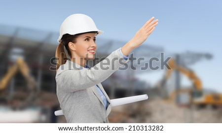 building, developing, construction and architecture concept - smiling woman in white helmet with blueprint