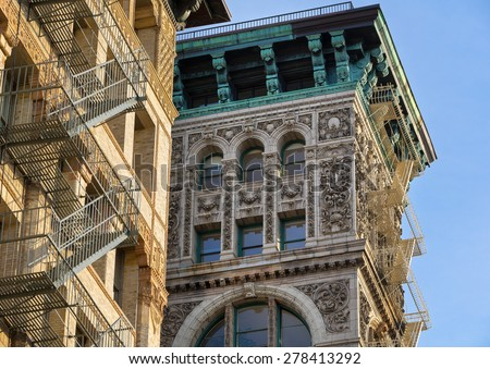 Building facade with terra cotta facade ornament and copper cornice on a Soho building in Manhattan. Painted iron fire escapes are often seen in Soho architecture. New York City - stock photo