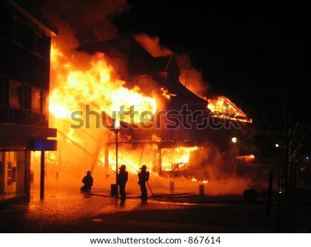 Building in a fire inferno, and some firefighters desperately trying to get control of the flames (some noise) - stock photo