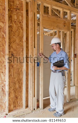 Building inspector checking building framing,electrical, phone - stock photo