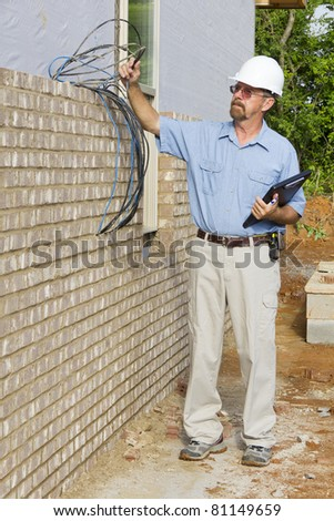 Building inspector checking electrical wires,phone lines, building framing,electrical and plumbing stub outs - stock photo