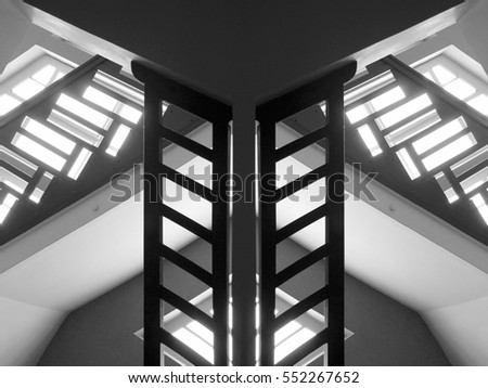 Building interior fragment with pitched roof / ceiling, windows and staircases. Abstract black and white photo on the subject of modern architecture.
