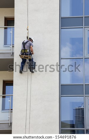 Building maintenance: Man working at height - stock photo