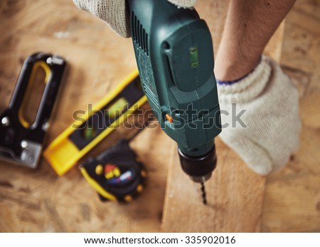 Building master with drilling machine. Professional carpenter working with wood and building tools in house.   - stock photo