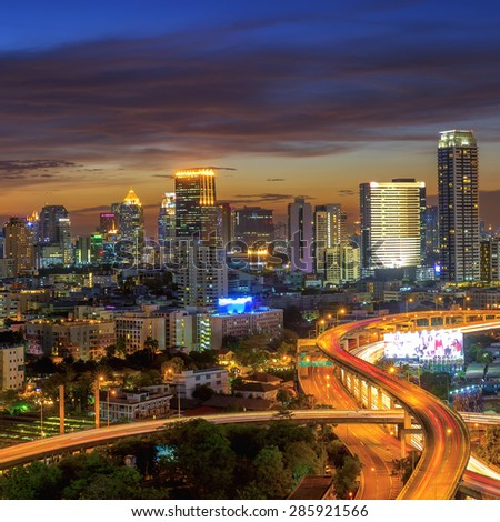 Building modern business district of Bangkok. S-shaped expressway in the foreground at twilight. - stock photo