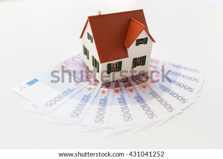 building, mortgage, investment, real estate and property concept - close up of home or house model and money - stock photo