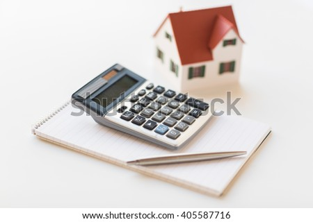 building, mortgage, real estate and property concept - close up of home model, house keys and notebook with pen - stock photo