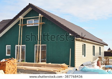 Building New House with Plastic Siding and Insulation Membrane on House Exterior Wall. House Construction