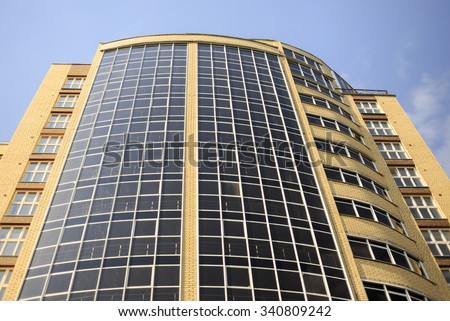 building of glass and bricks. a new high-rise office building of glass and yellow brick, bottom view - stock photo