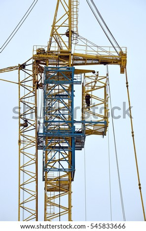 Building of tower crane with an additional telescopic joint at the construction site. Fragment