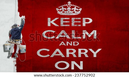 Building painter hanging from harness painting a red wall with white letters the motto Keep calm and carry on - stock photo