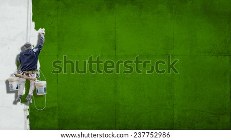 Building Painter hanging from harness painting a wall in green with lots of copy space for your own, message - stock photo