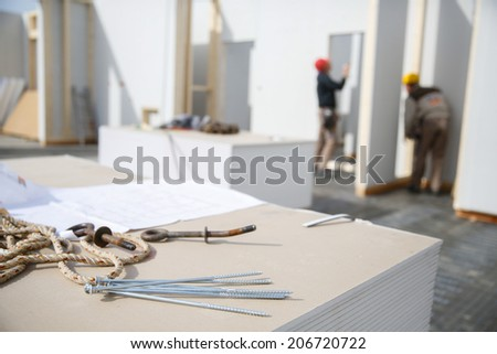 Building plan, screws and eye bolt  with workers in background at construction site - stock photo