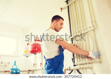 building, profession and people concept - builder or plumber working with water pipes in boiler room - stock photo