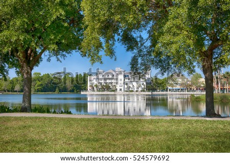 Building reflecting across a lake between to southern oak trees