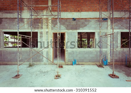 building residential construction house with scaffold steel for construction worker, wall made from brick, image used vintage filter