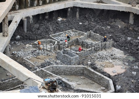 Building site,Masons building brick wall  of  a concrete pipe caps in a basement of a multi-storey building.The frame of  brick wall are used  for  pipe caps to provide a suitable stable foundation. - stock photo