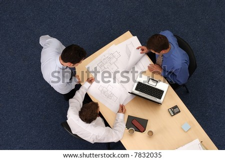 building strategy - three working business people over plans.Aerial shot taken from directly above the table