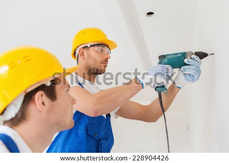 building, teamwork, working equipment and people concept - group of builders in hardhats with electric drill indoors - stock photo