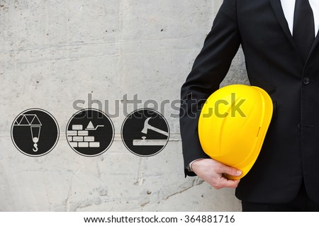 Building tomorrow world today. Digitally composed icon set over a picture of white collar worker holding hardhat in his hand while standing against concrete wall  - stock photo