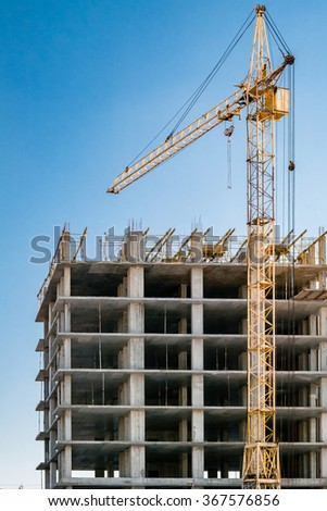 Building under construction and crane. - stock photo