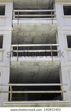 Building under construction with balconies and beams, urban architecture and exterior - stock photo