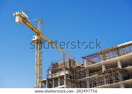 Building under construction with cranes against a blue sky.