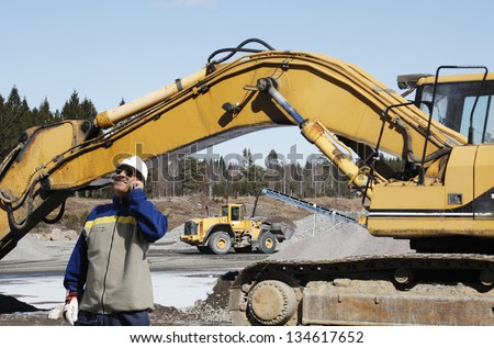 building worker directing bulldozers and trucks inside industrial area - stock photo