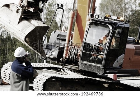 building worker directing large bulldozer and driver - stock photo