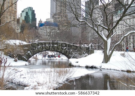Buildings and Gapstow bridge over the icy lake and snow at Central Park