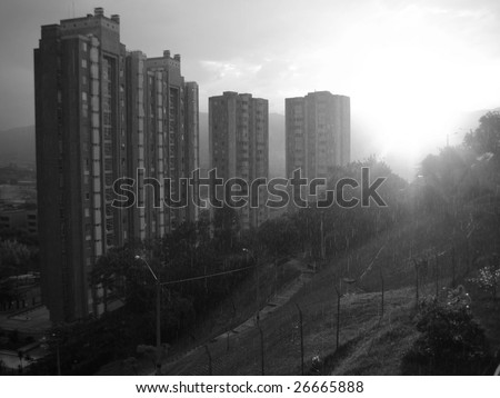 Buildings of Medellin, Colombia with the sun poking through the rain clouds, Antioquia province - stock photo
