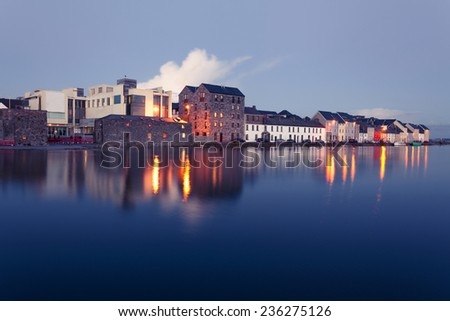 Buildings on the bank of the river during High tide in the city in dusk. Claddach, Galway, Ireland.