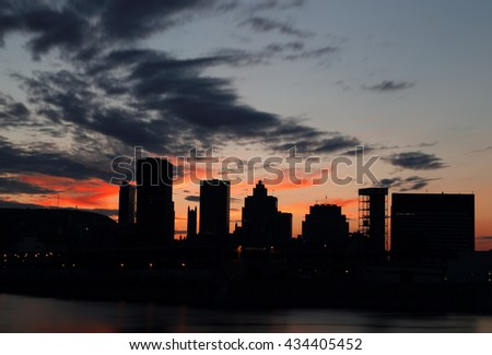 Buildings reflected in the water at sunset. Silhouettes of buildings reflected in the water at sunset. Montreal Downtown Panorama at sunset. Montreal over river at sunset with city lights. Sunset. - stock photo