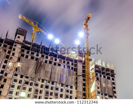 buildings under construction with cranes and illumination at dark night - stock photo