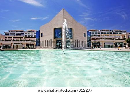 Buildings, water feature and fountain in Antonio Banderas Plaza in Puerto Banus Spain - stock photo