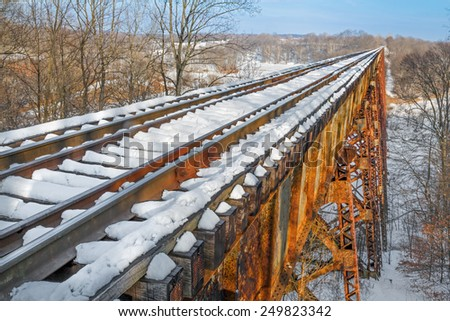 Built in 1905, Indiana's Tulip Trestle or Greene County Viaduct is one of the world's longest railroad bridges and is covered with snow in this wintry photograph. - stock photo