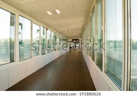 Built in walkway in train station. Windows on sides and long corridor. - stock photo