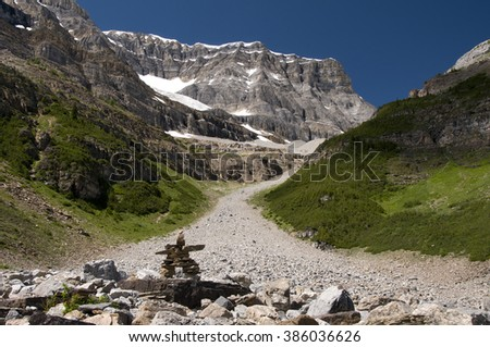 Built on a moraine, a modern inukshuk, or stone cairn serving as a signpost or landmark, marks the path forward on a scenic trail in Banff National Park, Alberta, Canada. - stock photo