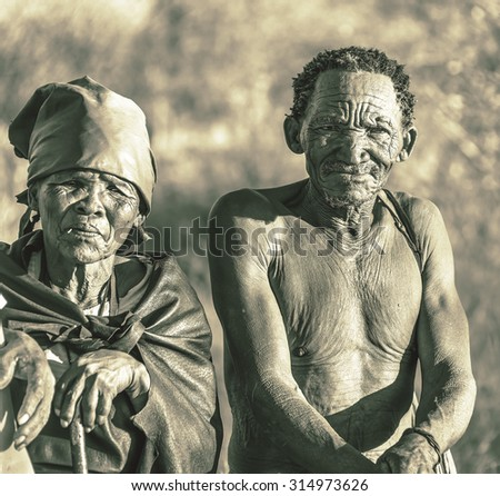 BUITEROS, NAMIBIA - JULY 17, 2014: Hunter Bushmen and their wives posing tourists. The Bushmens are members of various indigenous hunter-gatherer peoples of Southern Africa (stylized retro) - stock photo