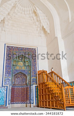 BUKHARA, UZBEKISTAN - APRIL 29, 2015: The medieval mihrab decorated with glazed colorful tiles and the modern wooden minbar at hall of the Great Mosque, on April 29 in Bukhara.