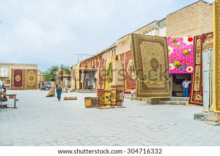 BUKHARA, UZBEKISTAN - APRIL 28, 2015: The rug merchants wait for tourists at the old carpet bazaar, on April 28 in Bukhara.