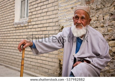 BUKHARA, UZBEKISTAN - October 6, 2015: Old Uzbek man sitting near his house in old town Bukhara, Uzbekistan