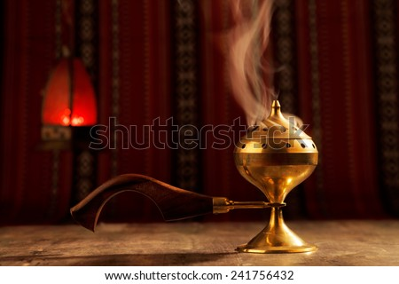 Bukhoor is usually burned in a mabkhara, a traditional incense burner It is customary in many Arab countries to pass bukhoor amongst the guests in the majlis  - stock photo